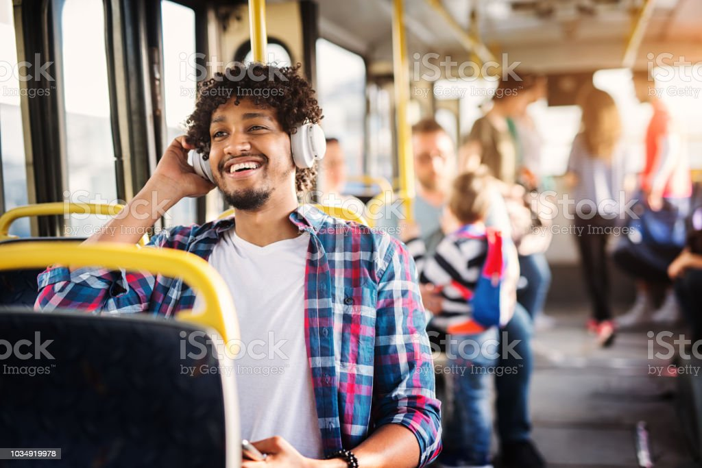 Young Afro-American man is sitting in a bus with headset on his head and listening to the music. stock photo