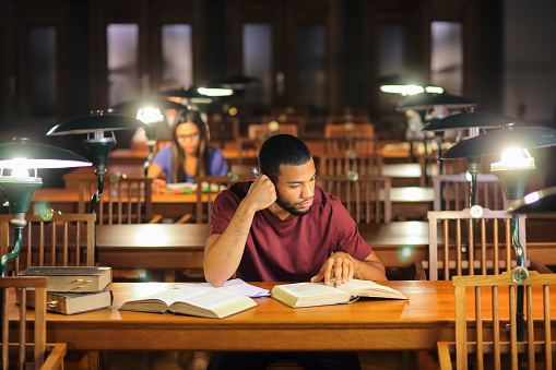 People reading books in the library. Afro-american man and asian woman sitting in the library reading room and studying for exam late at nigh.