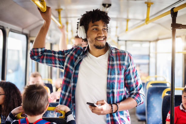 afroamerikanischen jungen mann mit kopfhörer auf dem kopf sucht weg während der fahrt in einem bus. - hauptverkehrszeit stock-fotos und bilder
