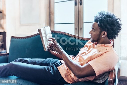 young afro-caribbean cuban reading book on sofa in old villa in Havana