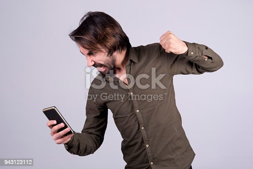 istock Young afro-haired grimaces at cellphone he holds 943123112