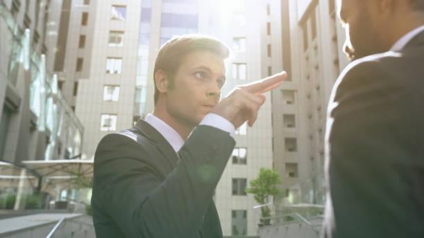 Joven empresario agresivo haciendo viendo el gesto empleado, jefe - foto de stock