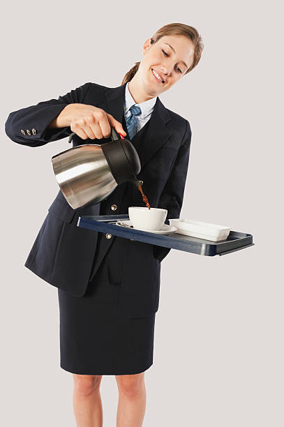 Young air hostess pouring hot beverage stock photo