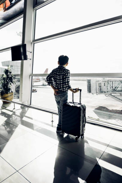 Junger Flugpassagier, der das Flugzeug im Abfluggate eines Flughafens betrachtet – Foto
