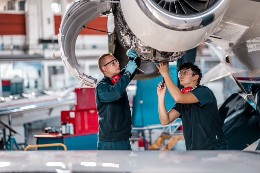 Two male aircraft maintenance mechanics inspect and check an airplane jet engine in the airport hangar.