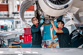 istock Young aircraft mechanics working on a jet engine in the hangar 1284111580