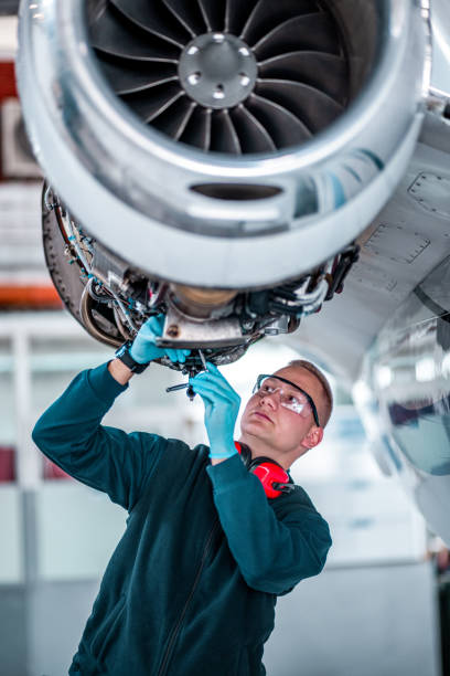 Young airplane mechanic works on a private jet stock photo