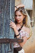 istock Young alluring cowgirl behind old wooden stable gates 530202313
