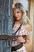 istock Young alluring cowgirl behind old wooden stable gates 530202315