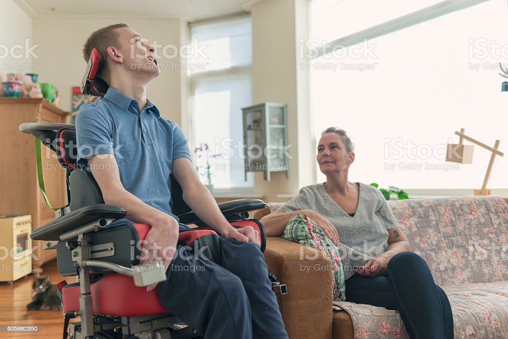 Young ALS patient with his mom stock photo
