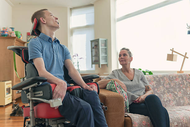 Young ALS patient with his mom Color image of a real life young physically impaired ALS patient spending time with his mother at home. He is happy. als stock pictures, royalty-free photos & images