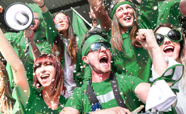Young amateur football fan supporters cheering with confetti watching local soccer cup match at stadium - Friends people group on green t shirts having excited fun on sport world championship final stock photo
