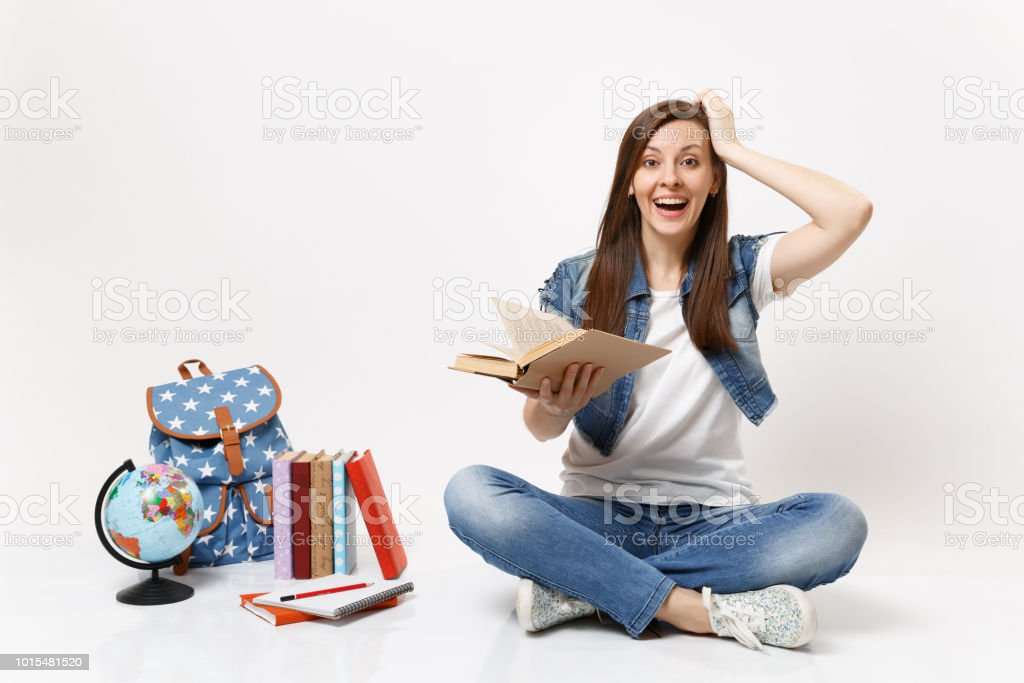 Young amazed laughing woman student in denim clothes hold book keeping hand near head sit near globe, backpack, school books isolated on white background. Education in high school university college. stock photo