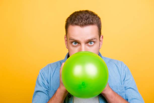 junge, ist erstaunt, stilvoller blonder mann bläst grüner ballon für geburtstagsparty und mit weit aufgerissenen augen auf gelbem hintergrund in die kamera schaut - ballonhose stock-fotos und bilder