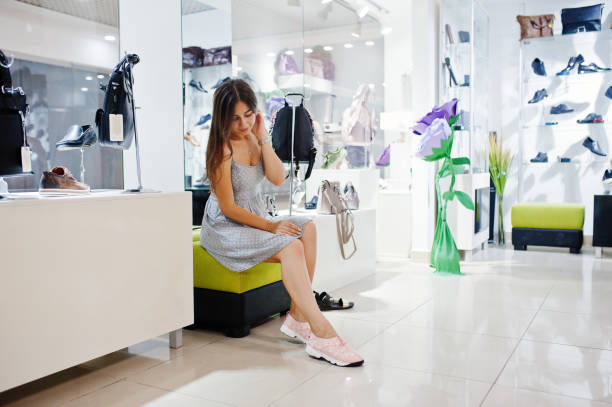 7eb5f79d3031 Young amazing woman trying on sport shoes in the shop while sitting. stock  photo