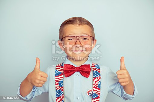 A little boy with big smile is dressed up in USA gear and ready to celebrate election day. He is smiling at the camera and wearing glasses and has his thumbs up. Exercise your right to vote.