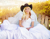 Young American Country bride portrait sitting, wearing a cowboy hat and smiling sweetly at the camera.