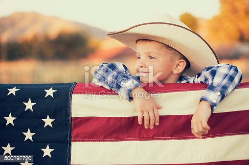 A young American boy dressed in cowboy western wear and cowboy hat displays the flag of the USA. He looks off camera and is smiling on the farm in Utah.