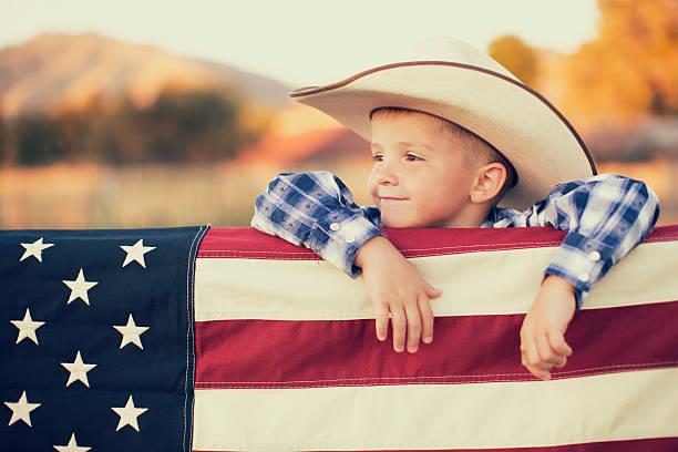 jeune américain cow-boy avec drapeau américain - mode de vie rural photos et images de collection