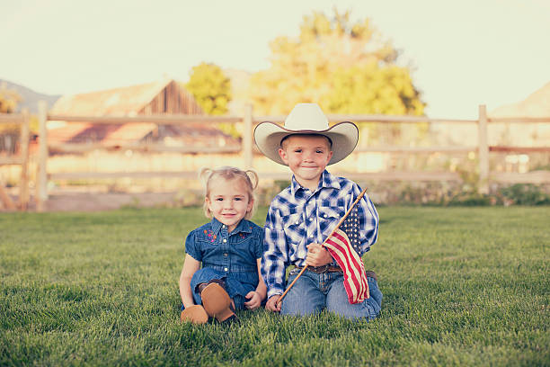 Young American Cowgirl and Cowboy with US Flag A young American girl and boy are dressed in western wear and holding the flag of the USA. They are proud of their country and are smiling while on a farm in Utah. happy 4th of july photos stock pictures, royalty-free photos & images
