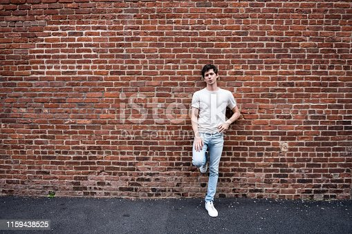 This is a color photograph of a young American man leaning against a red brick wall in Brooklyn, New York USA.