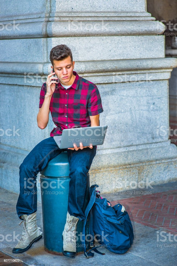 Young American Man working on laptop computer, talking on cell phone on street in New York. stock photo
