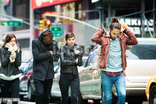 Young American people walking in Manhattan on bad, cold, Fall weather.