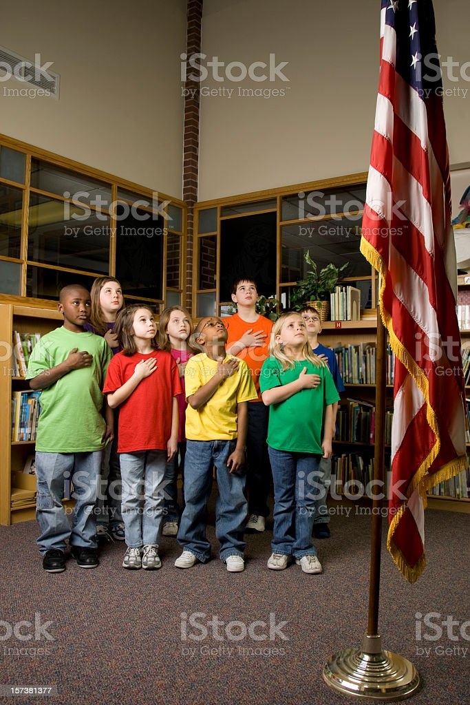 Young American students pledging allegiance to the flag stock photo