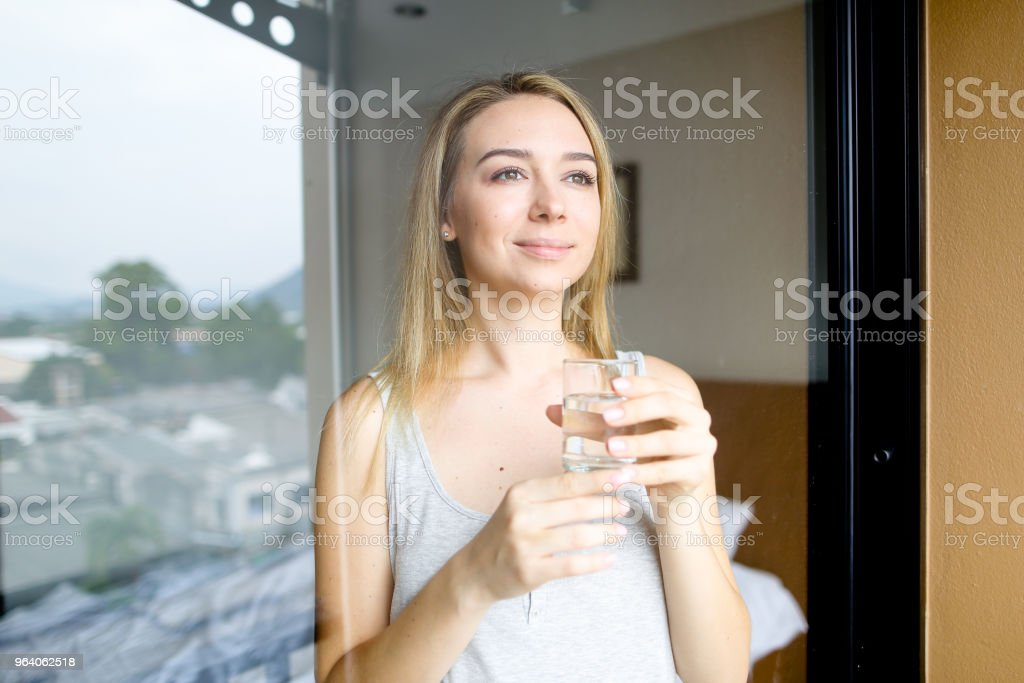 Young american woman drinking glass of water at hotel in morning - Royalty-free Adult Stock Photo