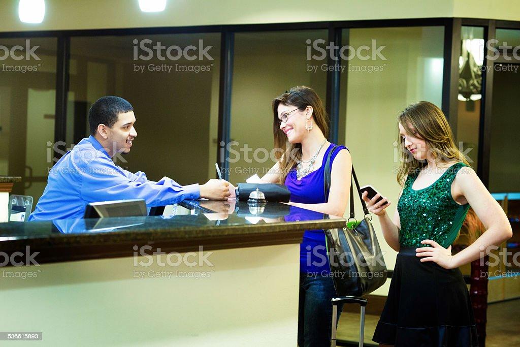 7b7e8ca73e76f1 Jeune femme américaine en vous inscrivant à la réception de l hôtel photo  libre de