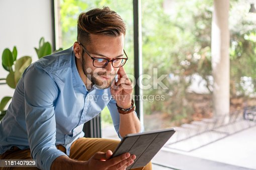 Young amiling Man looking at digital tablet
