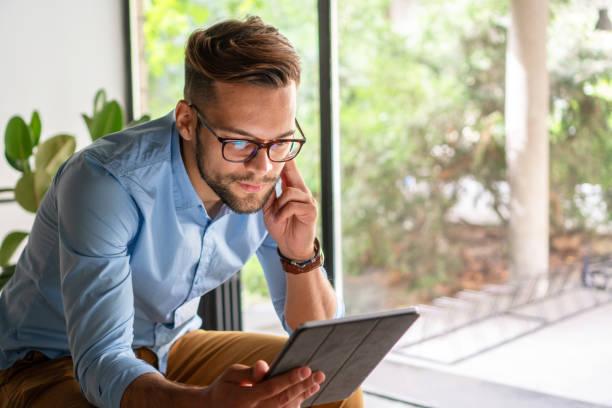 Young amiling Man looking at digital tablet stock photo