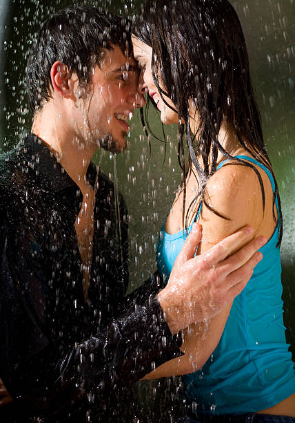 Young amorous happy couple embracing at summer rain stock photo