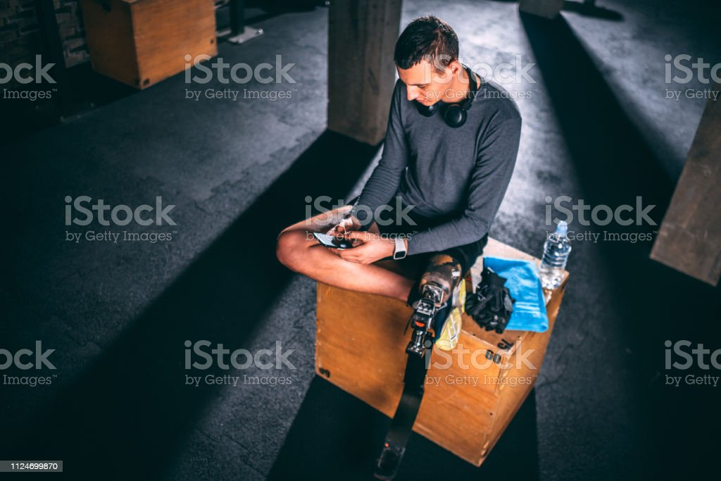 Young disabled man using a smart phone while sitting on a gym box in...