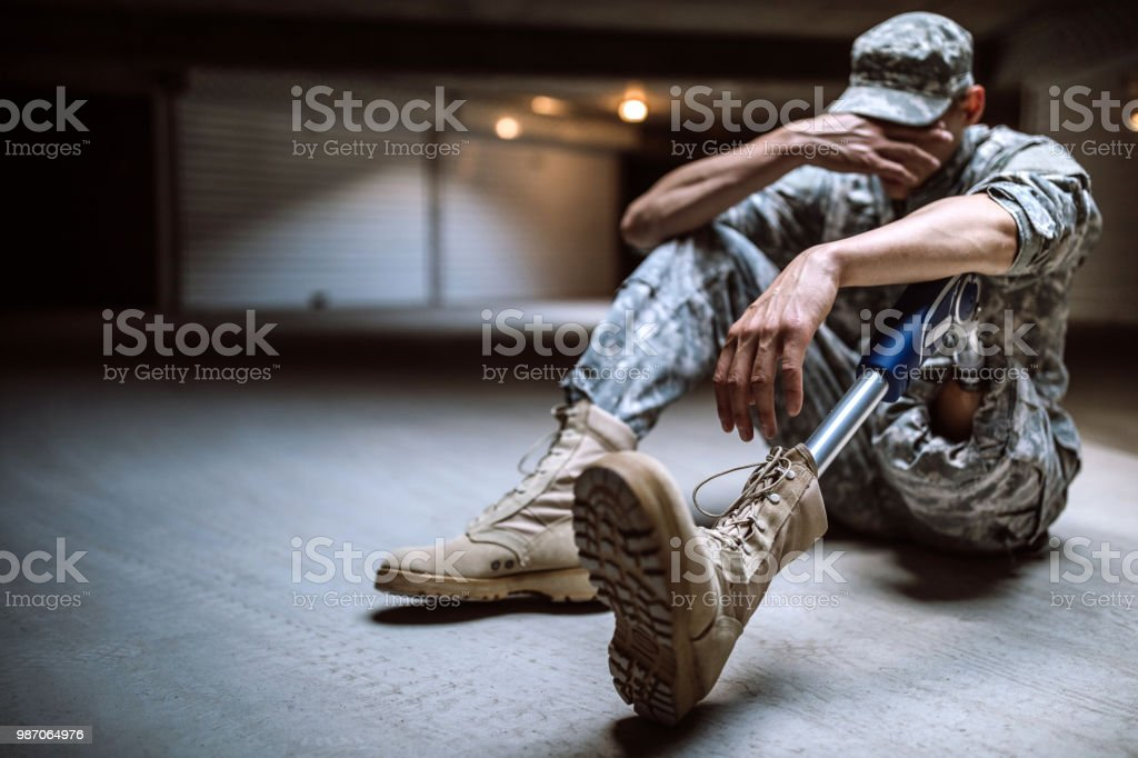 Young Amputee Soldier Crying In Bunker stock photo