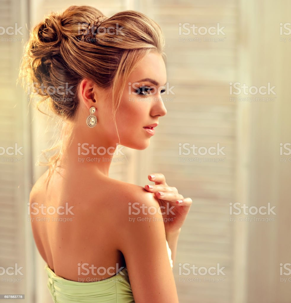 Young and attractive blond model dressed in evening gown and jewelry earings. stock photo