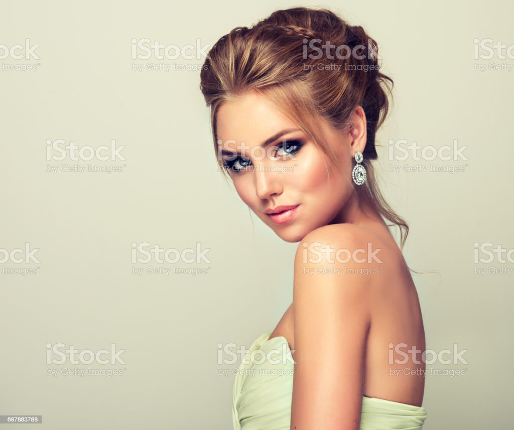 Young and attractive blond model dressed in evening gown and openwork earings. stock photo