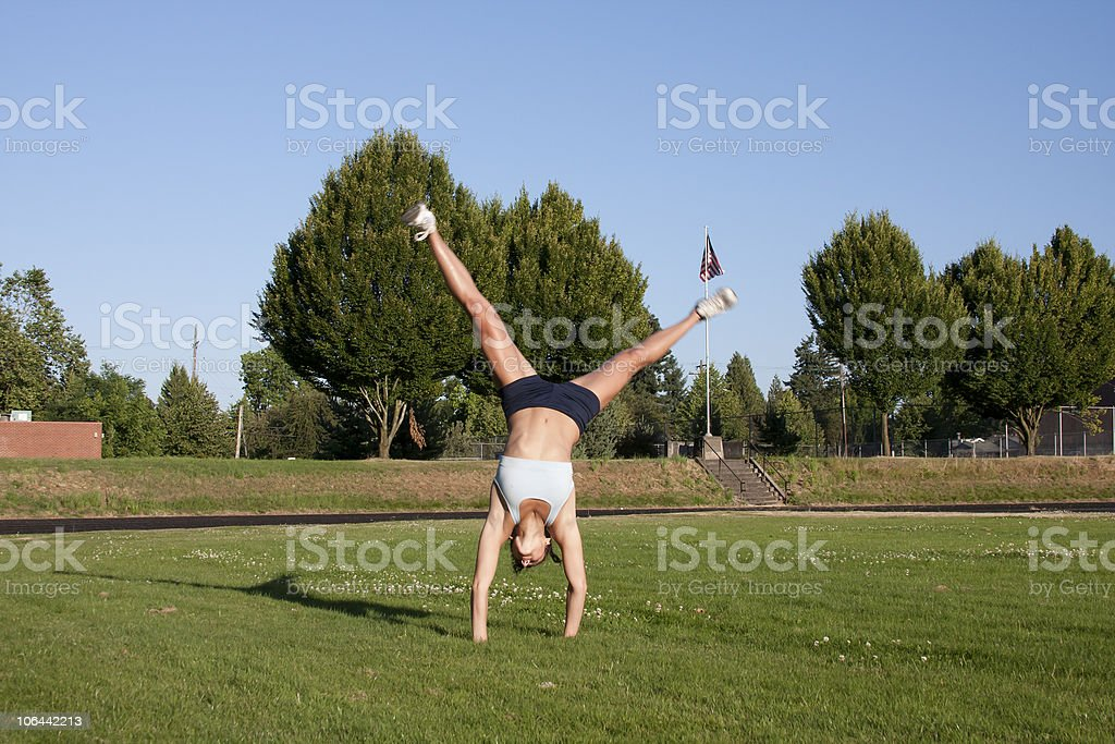 Young and Attractive Female Athlete does a cartwheel. royalty-free stock photo