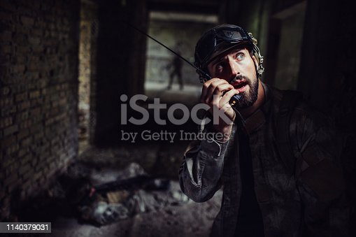 istock Young and bearded warrior is talking to portable radio. Also he is looking up. One of soldiers is lying on the floor while the third one is standing at the end of corridor. 1140379031