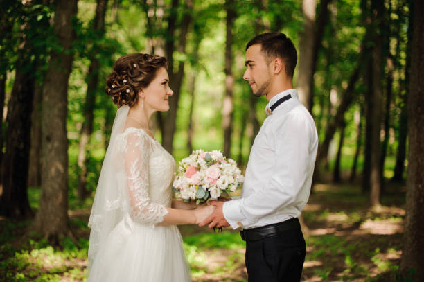 junge und schöne braut und bräutigam halten einander die hände - grüne wald hochzeiten stock-fotos und bilder