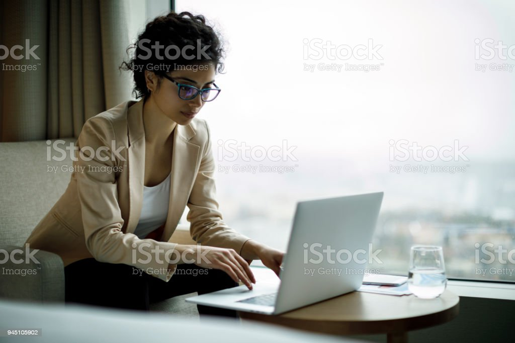 Young and beautiful businesswoman working on laptop in a hotel room stock photo
