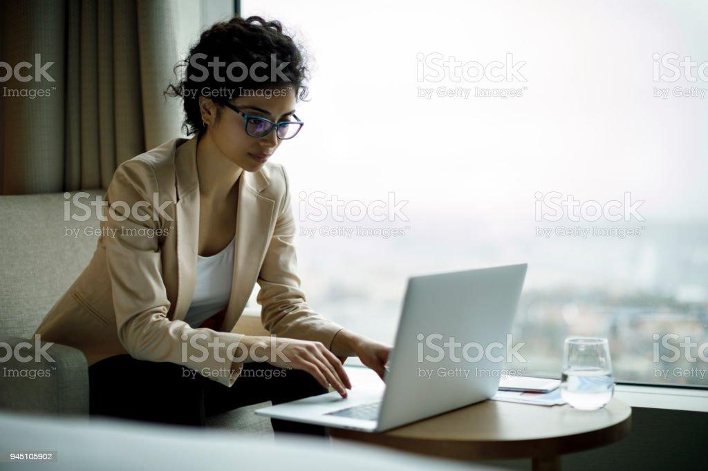 Junge und schöne geschäftsfrau arbeiten am Laptop in einem Hotelzimmer – Foto