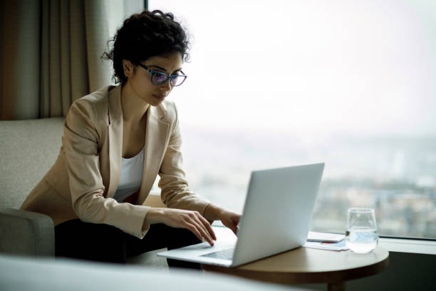 junge und schöne geschäftsfrau arbeiten am laptop in einem hotelzimmer - hotels in der türkei stock-fotos und bilder