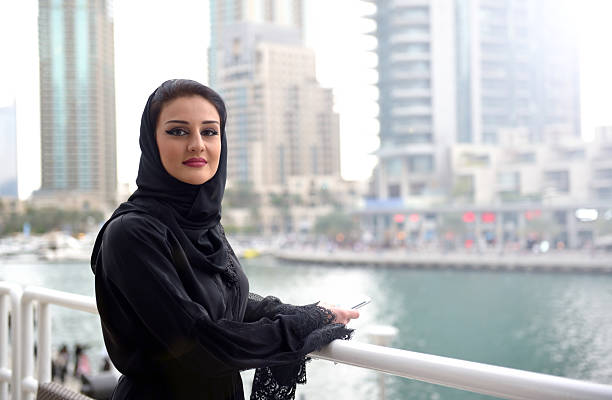Young and beautiful Emirati woman standing by the canal stock photo