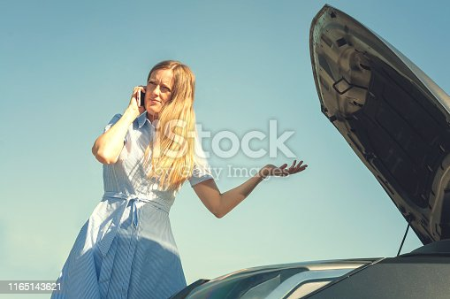 860373412 istock photo Young and beautiful girl near a broken car with an open hood. Problems with the car, does not start, does not work. 1165143621