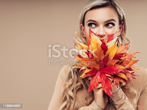 istock Young and beautiful girl with a bouquet of autumn leaves 1169645931