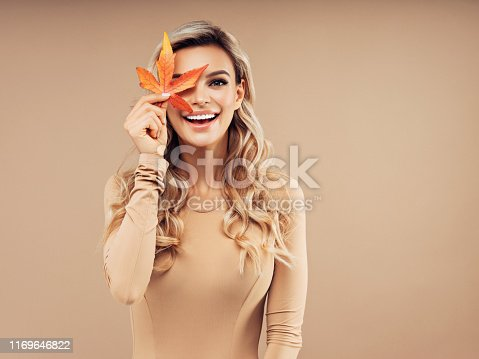 Young and beautiful girl with a bouquet of autumn leaves
