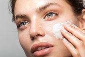 Close up studio shot of a beautiful woman with perfect skin, applying moisturizing cream