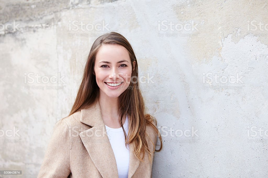 Young and beautiful woman against wall, portrait stock photo