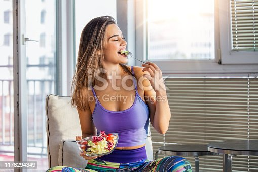 Young and beautiful woman enjoying heathy salad sitting at home with sunshine behind her. Healthy food concept Beautiful fit woman eating healthy salad after fitness workout